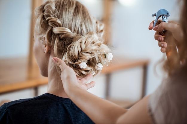 Vrouwelijke kapper die kapsel maakt aan blondevrouw in schoonheidssalon