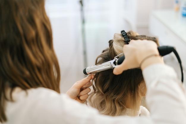 Vrouwelijke kapper die kapsel maakt voor jonge vrouw met blond haar in salon
