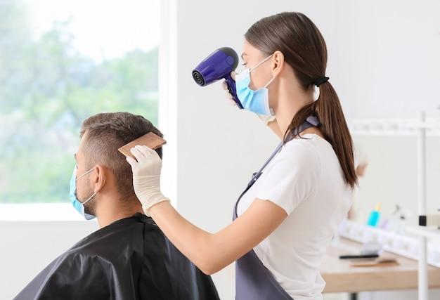 Vrouwelijke kapper die met cliënt in salon werkt tijdens coronavirusepidemie