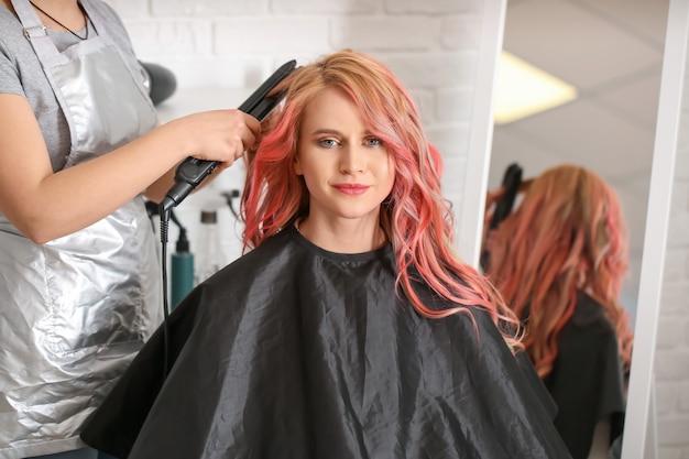 Vrouwelijke kapper doet haar van mooie jonge vrouw in salon