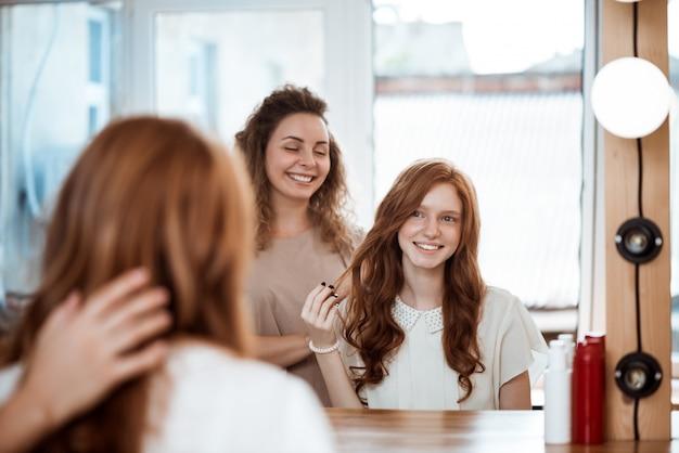 Vrouwelijke kapper en vrouw glimlachen, die in spiegel in schoonheidssalon kijken