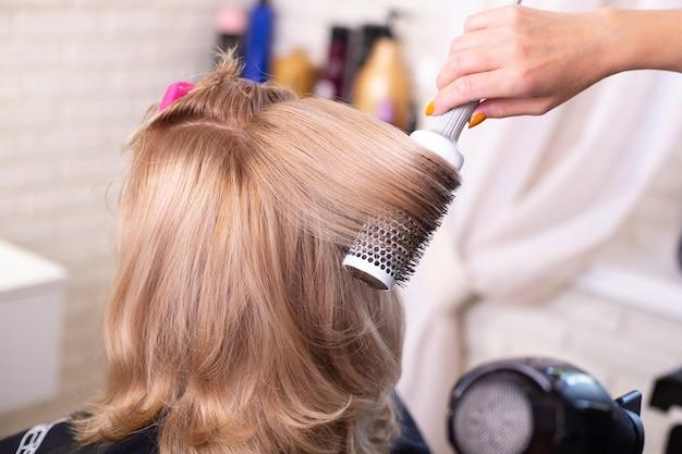 Vrouwelijke kapper hand borstelen en föhnen blonde haren in de schoonheidssalon