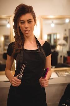 Vrouwelijke kapper houden haar krultang machine en haarborstel