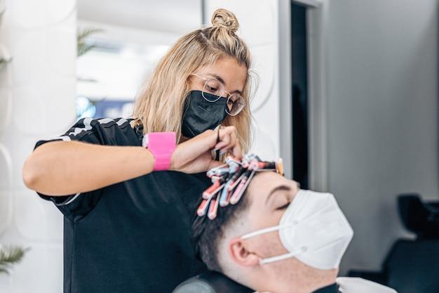 Vrouwelijke kapper krult het haar van een man met rollers tijdens het gebruik van een masker