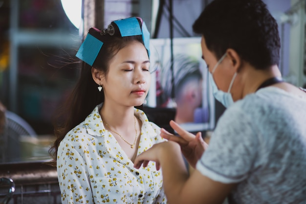 Vrouwelijke kapper permanent, gezicht make-up en het maken van kapsel tot schattige mooie jonge vrouw in schoonheidssalon