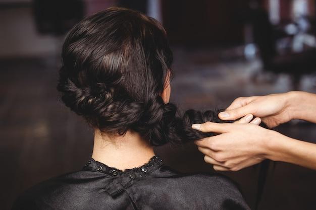 Vrouwelijke kapper styling klanten haar