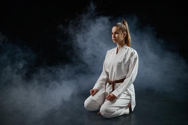 Vrouwelijke karateka op training in witte kimono zittend op de vloer. karatevechters op training, vechtsporten, vrouwen die vechten tegen concurrentie