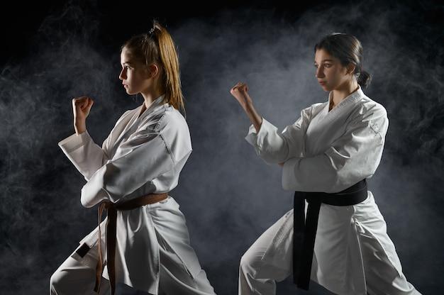 Vrouwelijke karateka's, training in witte kimono, gevechtshouding in actie. karatevechters op training, vechtsporten, vrouwen die vechten tegen concurrentie
