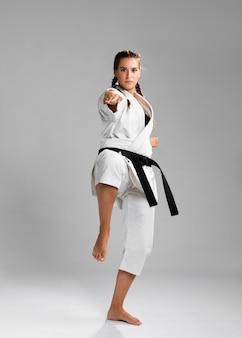 Vrouwelijke karatevechter die schop uitvoert die op grijze achtergrond wordt geïsoleerd