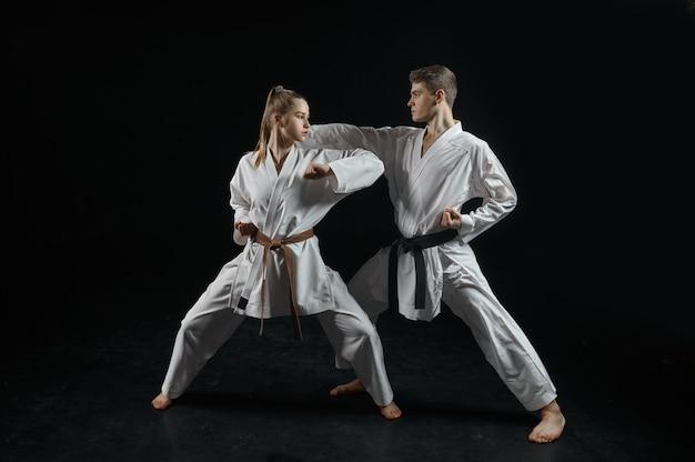 Vrouwelijke karatevechter op training met meester, witte kimono. karateka over training, vechtsporten, vechten