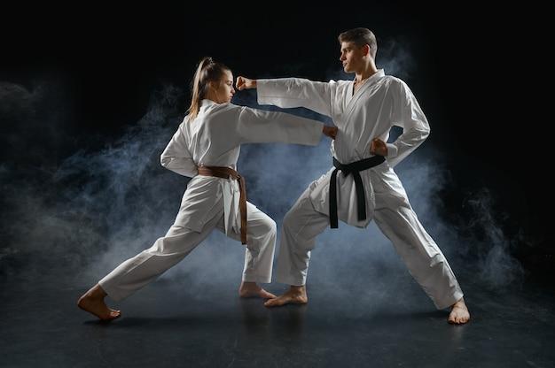 Vrouwelijke karatevechter op training met meester, witte kimono. karateka over training, vechtsporten, vechtwedstrijden