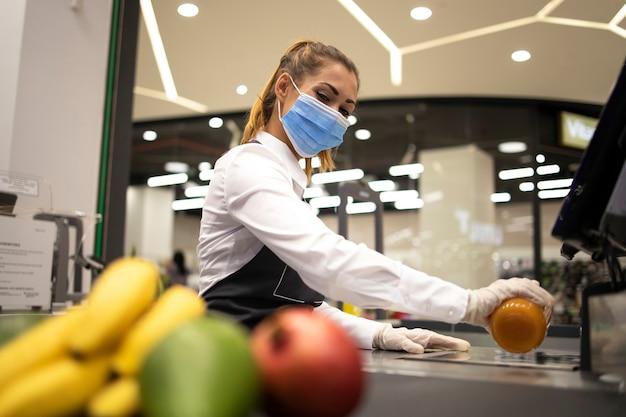 Vrouwelijke kassamedewerker in supermarkt die hygiënisch beschermingsmasker en handschoenen draagt tijdens risicovolle baan vanwege pandemie van het coronavirus
