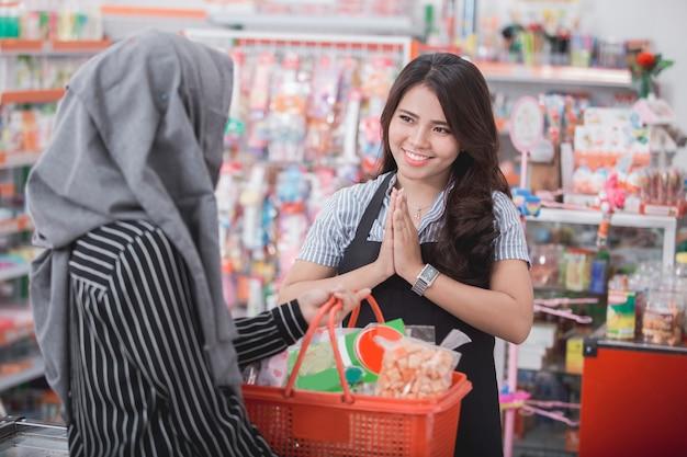 Vrouwelijke kassier die aan klant glimlacht
