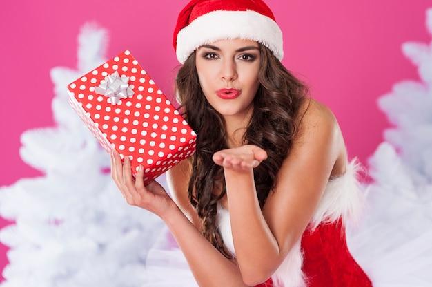 Vrouwelijke kerstman poseren met cadeau