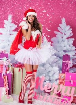 Vrouwelijke kerstman poseren met geschenken
