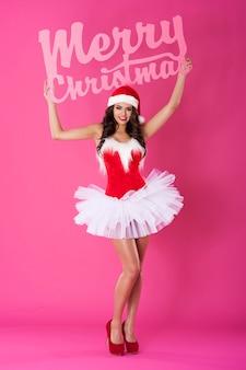Vrouwelijke kerstman poseren met vrolijk kerstfeest belettering