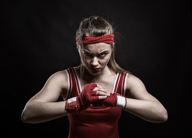 Vrouwelijke kickbokser in rode handschoenen en sportkleding, zwarte achtergrond. vrouw op bokstraining