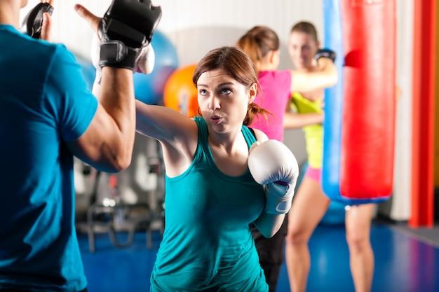 Vrouwelijke kickbokser met trainer in het sparren