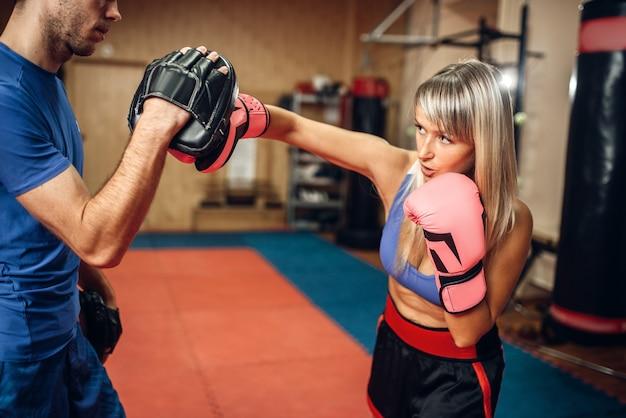 Vrouwelijke kickbokser op training met mannelijke personal trainer in pads, sportschool interieur. vrouw bokser maakt hand punch op training, kickboksen praktijk