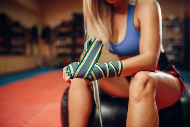 Vrouwelijke kickbokser zittend op bokszak in sportschool