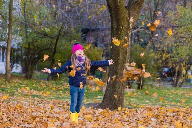 Vrouwelijke kind in heldere hoed spelen met gebladerte buitenshuis