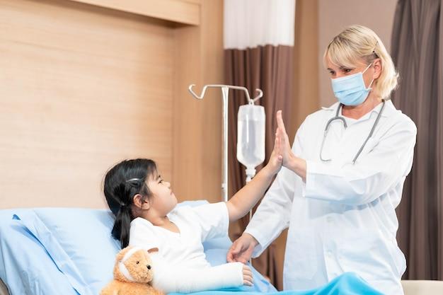 Vrouwelijke kinderarts arts en kind patiënt met teddybeer in het gezondheid medisch centrum