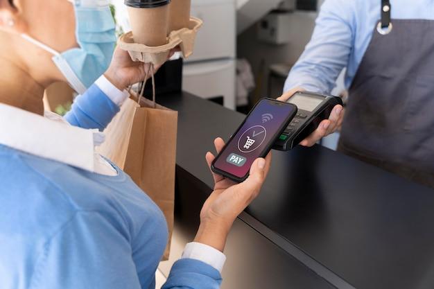 Vrouwelijke klant betaalt afhaalmaaltijden met smartphone