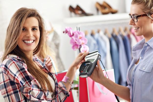 Vrouwelijke klant betaalt voor kleding in boetiek