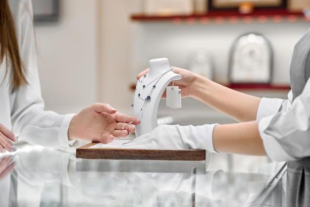 Vrouwelijke klant controleert de ketting gepresenteerd door een juwelier woker in een juwelierszaak