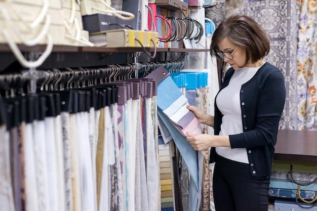 Vrouwelijke klant die binnenlandse stoffen kijkt