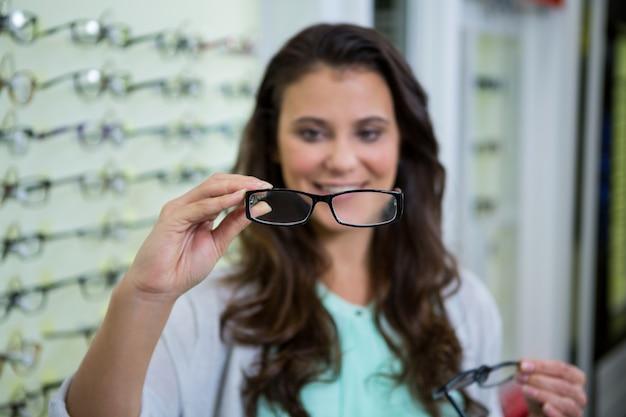 Vrouwelijke klant die bril in optische opslag kiezen