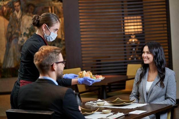 Vrouwelijke klant die dankbaar kijkt naar een server in masker die een bord met besteld eten naar hun tafel brengt