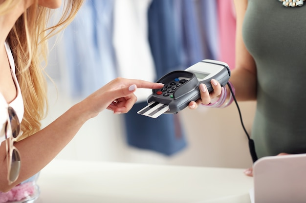 Vrouwelijke klant die in de winkel met creditcard betaalt