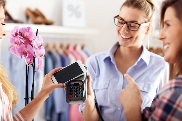 Vrouwelijke klant die in winkel met creditcard betaalt