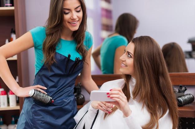 Vrouwelijke klant die laat zien welk kapsel ze wil op mobiele telefoon
