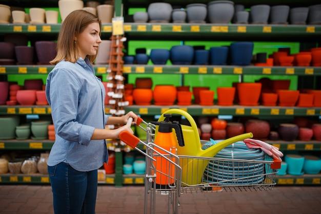 Vrouwelijke klant die met karretjeshulpmiddelen voor tuinieren koopt. vrouw kiezen van apparatuur in de winkel voor de sierteelt, de aankoop van het bloemistinstrument