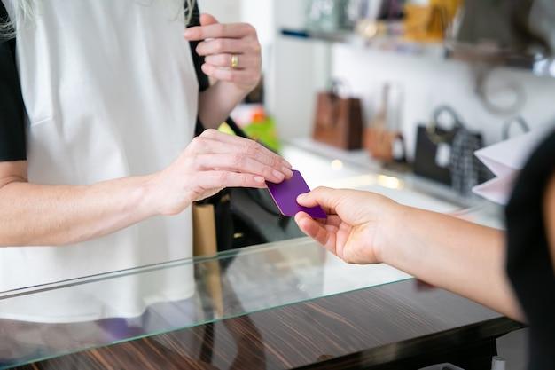 Vrouwelijke klant die voor aankoop met creditcard in kledingwinkel betaalt, lege kaart aan kassier over bureau geeft. bijgesneden schot, close-up van handen. winkelen of kopen concept