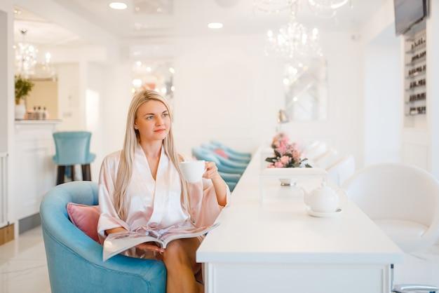 Vrouwelijke klant drinkt koffie in de schoonheidssalon.