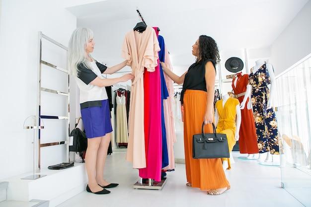 Vrouwelijke klant en winkelbediende samen browsen jurken op rek gericht, kleding kiezen in fashion store. volledige lengte. winkelen of winkelconcept