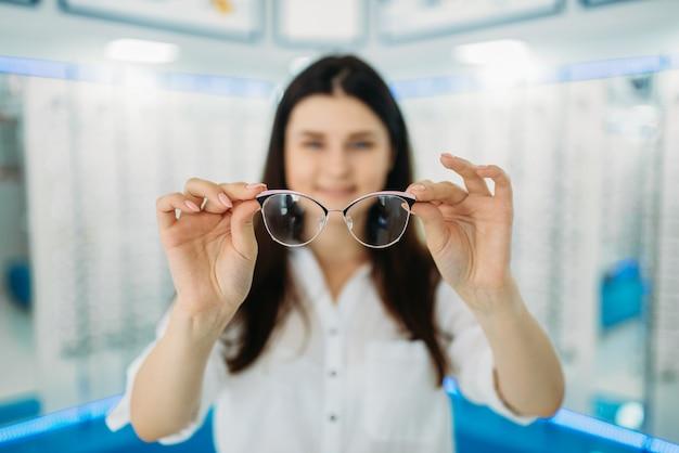 Vrouwelijke klant houdt bril in de hand, optische winkel