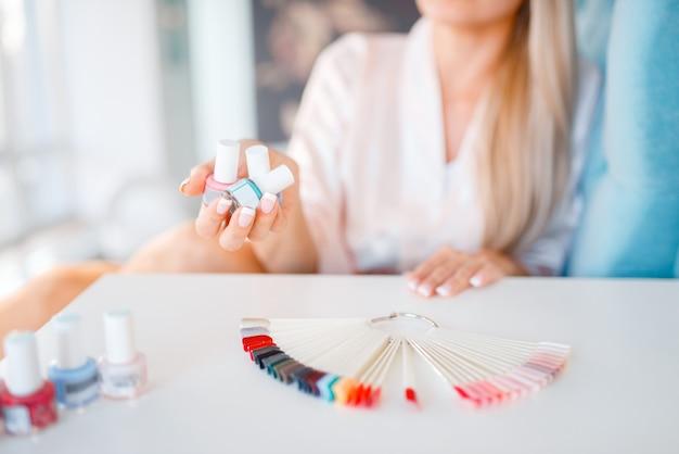Vrouwelijke klant houdt nagellakflessen