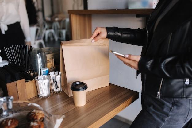 Vrouwelijke klant houdt telefoon vast voor contactloze betaling en afhaalpakket met eten en kopje koffie