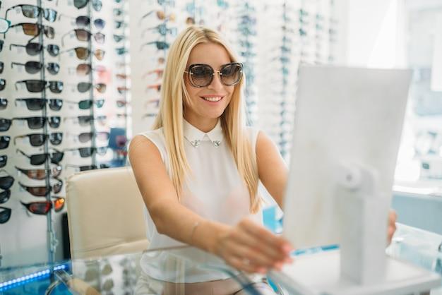 Vrouwelijke klant in zonnebril kijkt naar de spiegel in optica winkel.