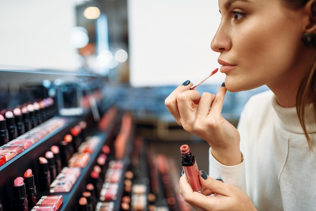 Vrouwelijke klant lip liner testen in make-up shop