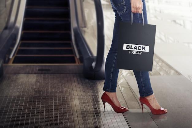 Vrouwelijke klant met black friday papieren zak