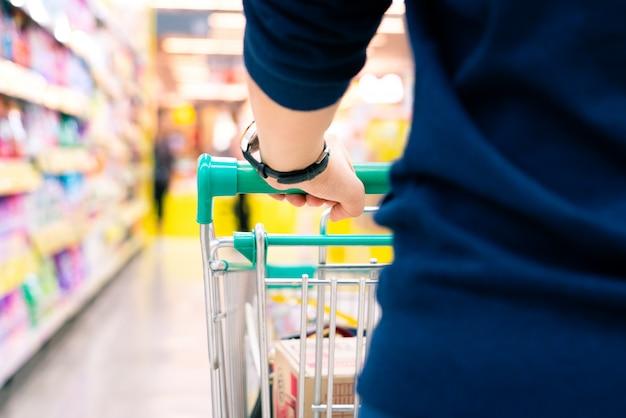 Vrouwelijke klant met karretje met vage motie van suppermarket warenhuis