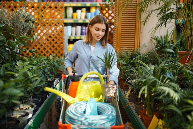 Vrouwelijke klant met karretjeshulpmiddelen voor bloemisterij. vrouw die apparatuur in de winkel koopt voor de bloementeelt, de aankoop van het bloemistinstrument