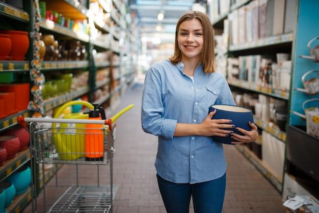 Vrouwelijke klant met pot, winkel voor tuinieren. vrouw die apparatuur in de winkel koopt voor de bloementeelt, de aankoop van het bloemistinstrument