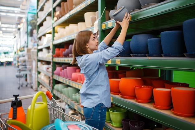 Vrouwelijke klant op de plank met potten, winkel voor tuinieren. vrouw die apparatuur in de winkel koopt voor de bloementeelt, de aankoop van het bloemistinstrument