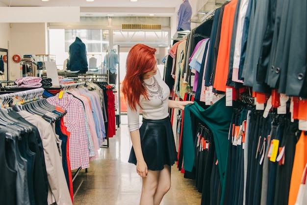 Vrouwelijke klant plukken kleren in de winkel